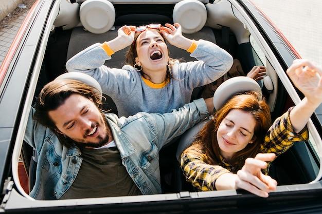 Lächelnde frauen und positiver mann, die spaß im auto haben