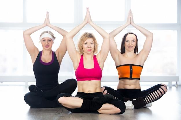 Lächelnde frauen yoga-klasse genießen