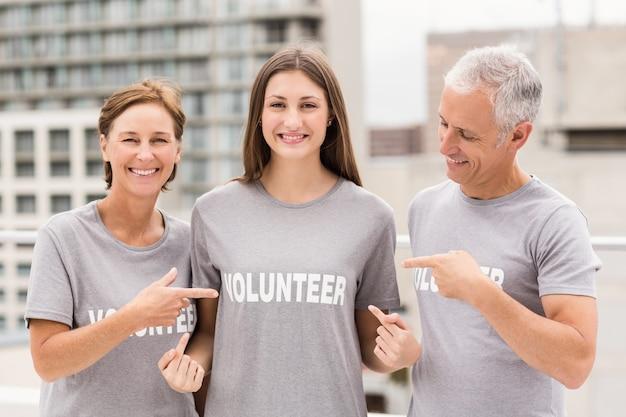 Lächelnde freiwillige, die auf hemd zeigen