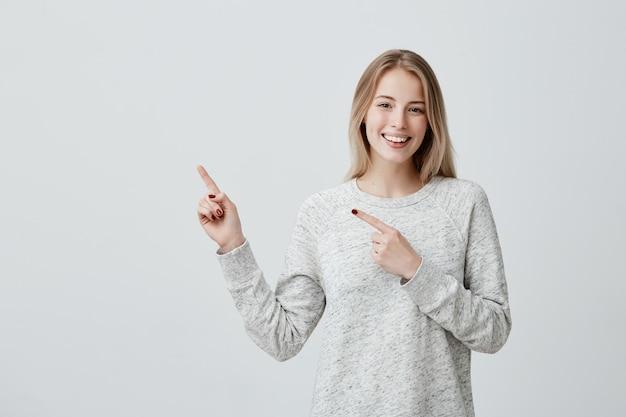 Lächelnde freudige frau, die mit dem finger auf copyspace zeigt