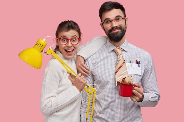 Lächelnde freudige junge frauen- und mann-nerds stehen eng beieinander, arbeiten bei der vorbereitung und beendigung gemeinsamer aufgaben zusammen, halten tischlampe und becher mit getränk