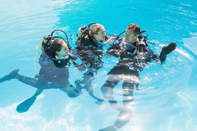 Lächelnde freunde auf unterwasseratemgerättraining im swimmingpool