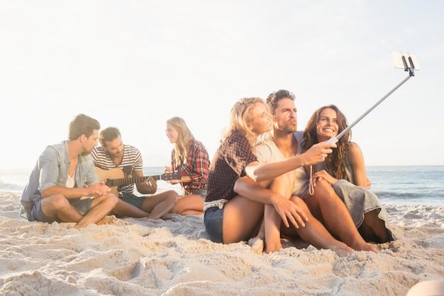 Lächelnde freunde, die auf dem sand singt und selfies nimmt sitzen