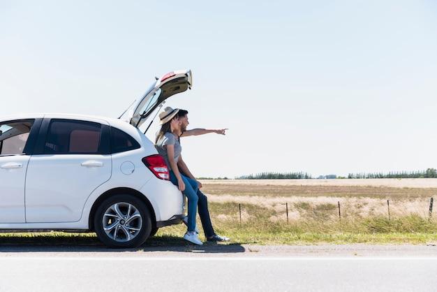 Lächelnde freunde, die auf einem auto zeigen auf etwas sitzen