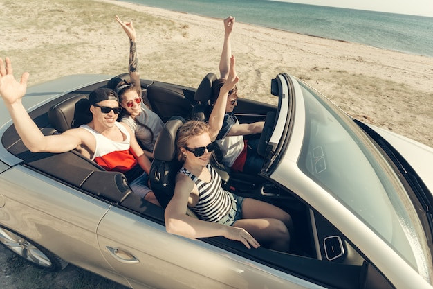 Lächelnde freunde, die auto in der nähe des meeres fahren und spaß haben