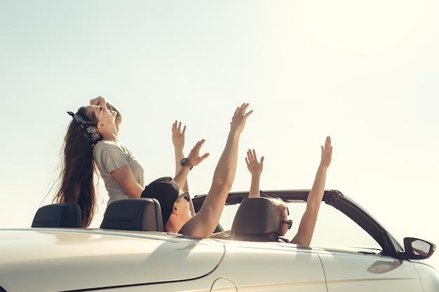 Lächelnde freunde, die auto nahe dem meer fahren und spaß haben