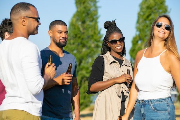 Lächelnde freunde, die mit bierflaschen während des feiertags stehen. gruppe junge leute, die während des sonnigen tages sich entspannen. freizeit