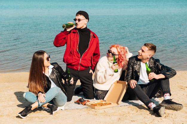 Lächelnde freunde, die party am strand haben