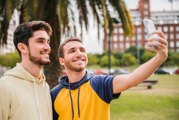 Lächelnde freunde, die selfie im park nehmen