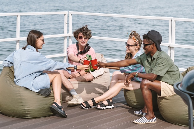 Lächelnde freunde, die sich in sitzsäcken auf dem pier ausruhen und mit plastikbechern und bierflaschen anstoßen