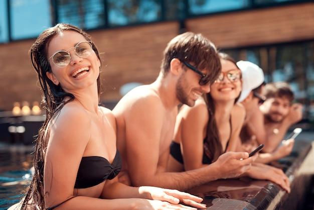 Lächelnde freunde, die smartphone am poolside verwenden