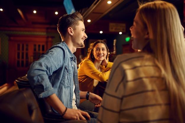 Lächelnde freunde entspannen sich an der theke in der bar. gruppe von menschen entspannen in der kneipe, nachtlebensstil, freundschaft, ereignisfeier
