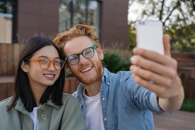 Lächelnde freunde influencer mit handy-videoaufnahme im freien