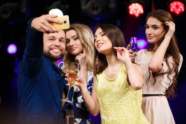 Lächelnde freunde mit gläsern champagner und smartphone, die selfie im verein nehmen