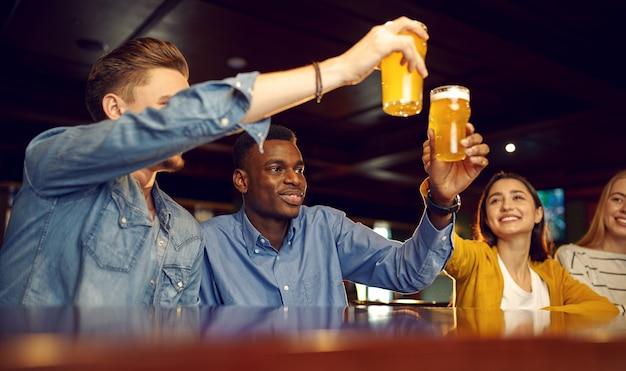 Lächelnde freunde trinken bier an der theke in der bar. gruppe von menschen entspannen in der kneipe, nachtlebensstil, freundschaft, ereignisfeier