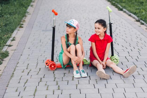 Lächelnde freundinnen, die auf ihren trittrollern im park sitzen