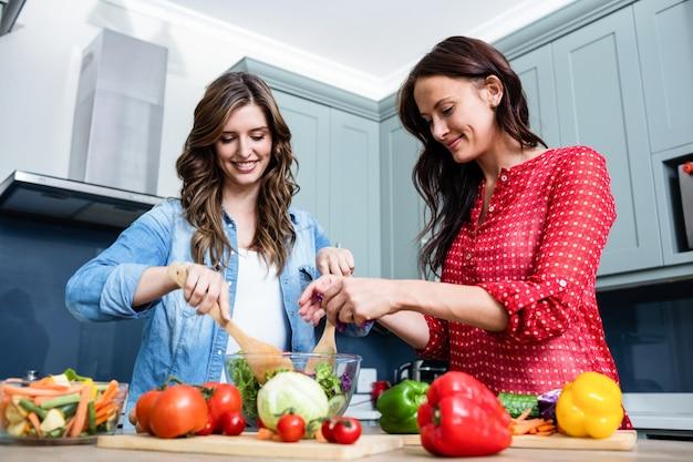 Lächelnde freundinnen, die gemüsesalat zubereiten