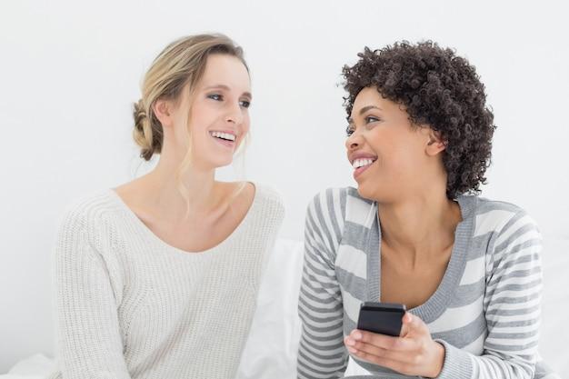 Lächelnde freundinnen, die textnachricht auf bett lesen