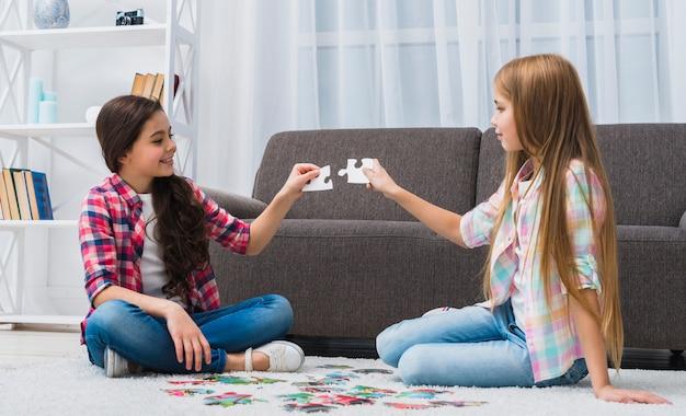 Lächelnde freundinnen, die versuchen, puzzlestück zu hause anzuschließen