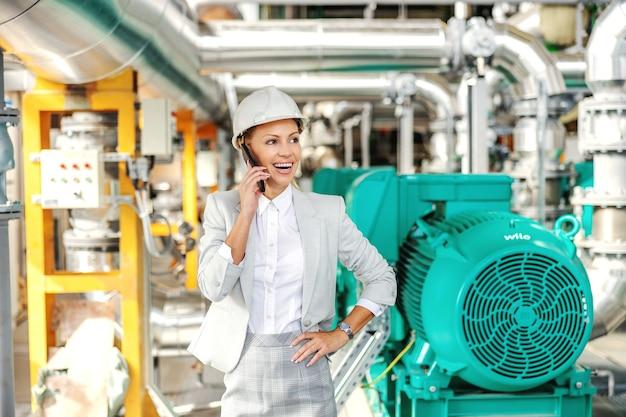 Lächelnde freundliche geschäftsfrau mit helm auf kopf, der im kraftwerk mit hand auf hüfte steht und mit geschäftspartner am telefon spricht.