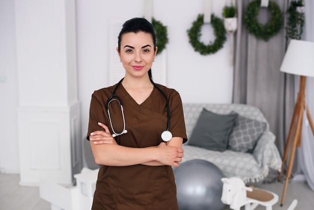 Lächelnde freundliche kinderarztfrau mit stethoskop, das braune medizinische robe trägt. gesundheitswesen und medizinisches konzept.