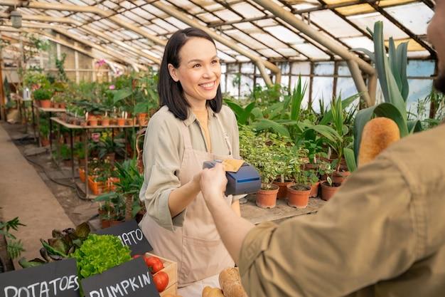 Lächelnde freundliche verkäuferin, die zahlung hält, während kunde mit kontaktloser karte am bauernmarkt zahlt
