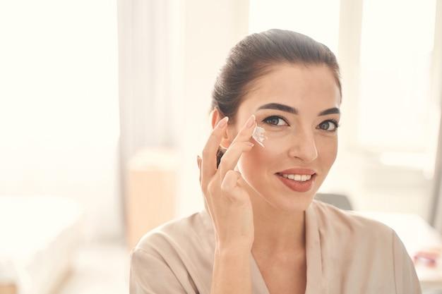 Lächelnde fröhliche dame, die morgens zeit mit schönheitsbehandlungen zu hause verbringt, während sie sanfte augencreme verwendet using