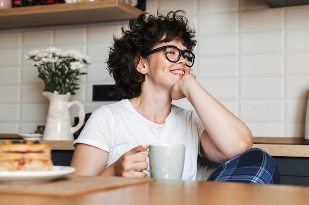 Lächelnde fröhliche frau, die leckeres frühstück hat, während sie zu hause in der küche sitzt und kaffee trinkt