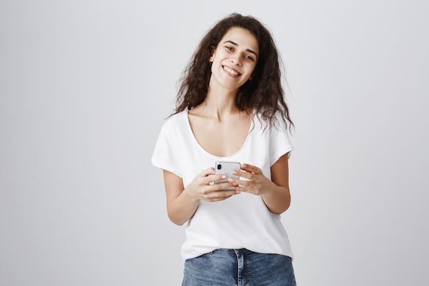 Lächelnde fröhliche frau mit handy, online einkaufen