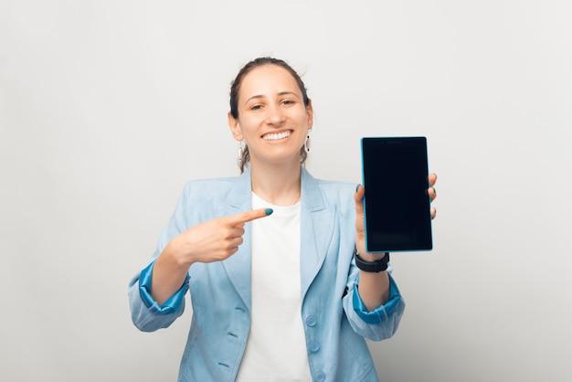 Lächelnde fröhliche frau zeigt auf den bildschirm des tablets.