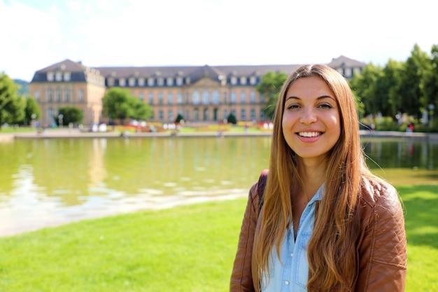 Lächelnde fröhliche junge frau vor dem neuen schloss von stuttgart, deutschland