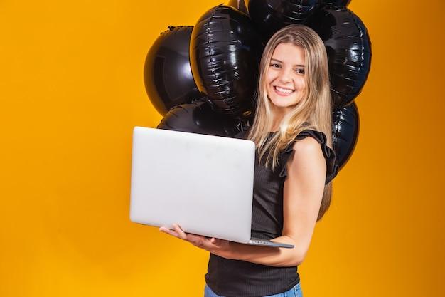 Lächelnde fröhliche lustige junge brünette frau 20er jahre mit laptop-pc auf hellgelbem hintergrund mit luftballon-studioporträt. verkauf am schwarzen freitag