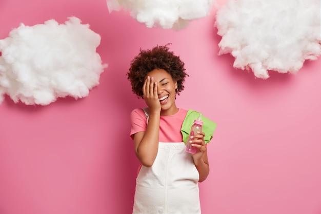 Lächelnde fröhliche schwangere frau macht gesichtspalme hält fütterungsflasche und trägt babys bodysuit auf schulterposen