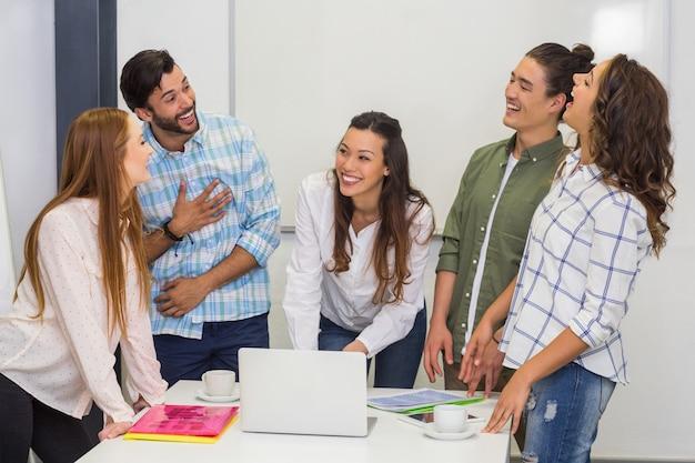 Lächelnde führungskräfte, die während eines meetings im konferenzraum interagieren