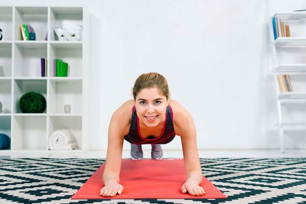 Lächelnde geeignete frau, die zu hause planke auf roter matte im wohnzimmer tut