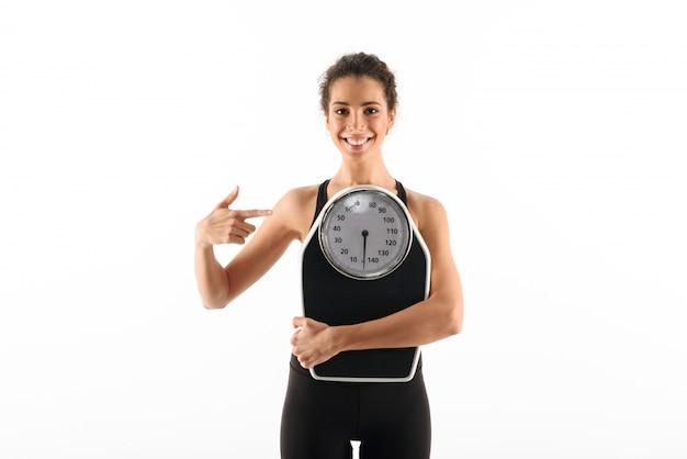 Lächelnde gelockte brunetteeignungsfrau, die gewichtungsskalen hält