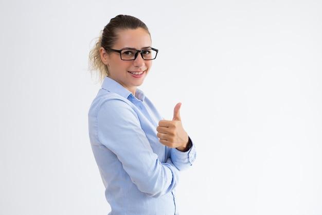 Lächelnde geschäftsdame, die sich daumen zeigt und kamera betrachtet
