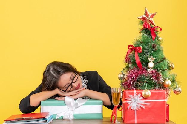 Lächelnde geschäftsdame im anzug mit brille, die auf ihrem geschenk schläft und an einem tisch mit einem weihnachtsbaum darauf im büro sitzt