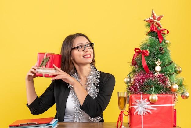Lächelnde geschäftsdame im anzug mit brille, die ihr geschenk hält und an einem tisch mit einem weihnachtsbaum darauf im büro sitzt