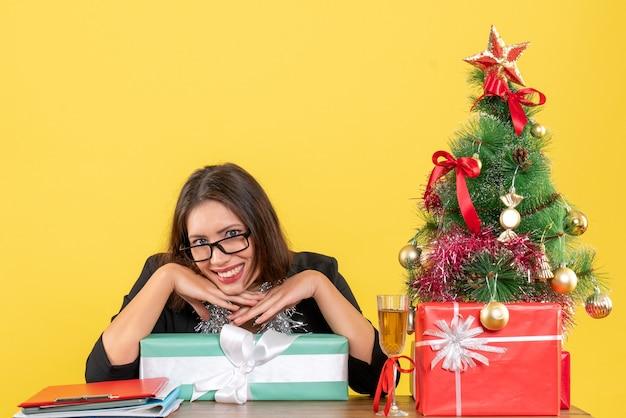 Lächelnde geschäftsdame im anzug mit brille, die ihr geschenk zeigt und an einem tisch mit einem weihnachtsbaum darauf im büromaterial sitzt