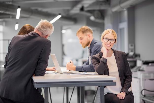 Lächelnde geschäftsfrau am arbeitsplatz während ihr kollege, der im büro sich bespricht