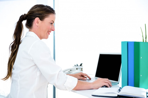 Lächelnde geschäftsfrau, an ihrem schreibtisch, der auf ihrem laptop schreibt