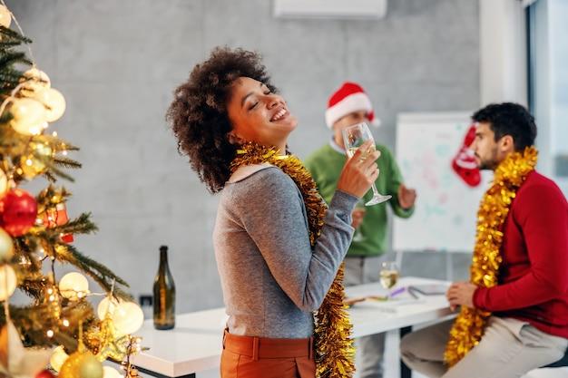 Lächelnde geschäftsfrau der gemischten rasse, die weihnachten an der firma feiert.