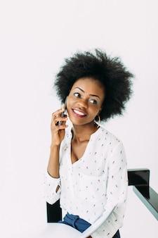 Lächelnde geschäftsfrau des afroamerikaners der junge, die das telefon, lokalisiert auf weiß verwendet