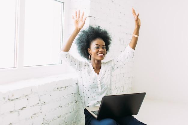 Lächelnde geschäftsfrau des afroamerikaners der junge, die den laptop, sitzend auf dem boden verwendet