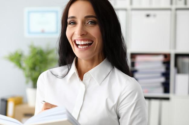 Lächelnde geschäftsfrau des erfolgs, die tagebuch hält