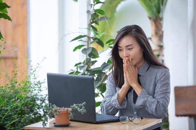 Lächelnde geschäftsfrau, die am laptop im café arbeitet