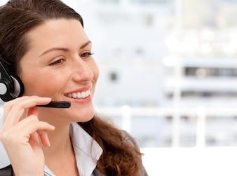 Lächelnde geschäftsfrau, die am telefon mit kopfhörern spricht