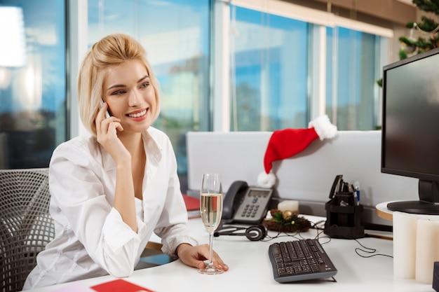 Lächelnde geschäftsfrau, die am telefon spricht, das im büroweihnachtstag arbeitet.