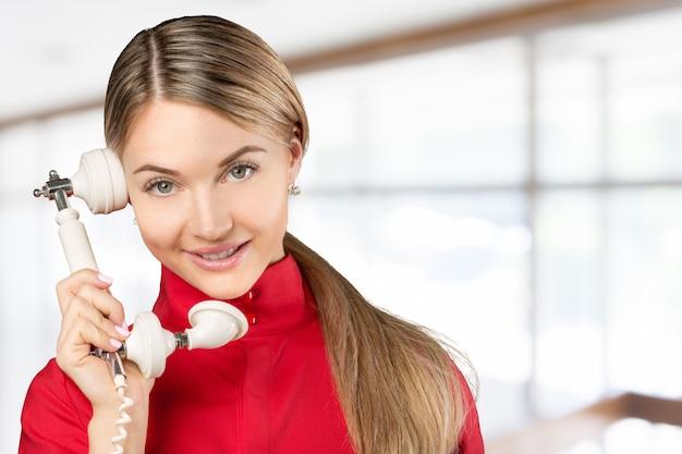 Lächelnde geschäftsfrau, die am telefonrohr lokalisiert auf einem weißen hintergrund spricht